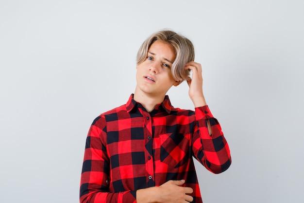 어린 십대 소년이 체크 셔츠를 입고 머리를 긁적이며 사려깊은 전면 전망을 보고 있습니다.