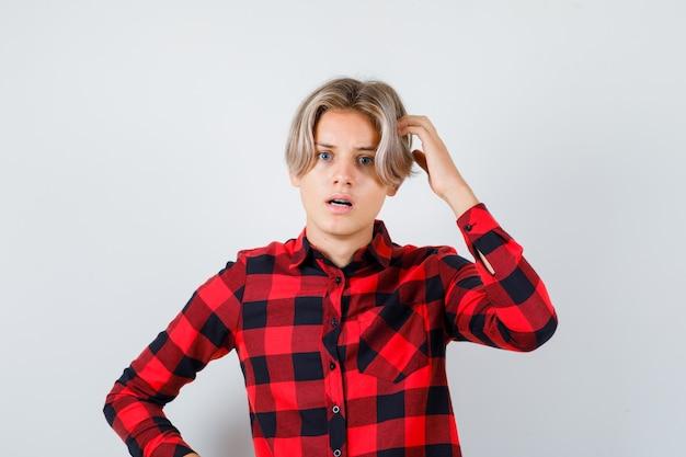 チェックのシャツで口を開けて混乱しているように見える間、彼の頭を引っ掻く若い十代の少年、正面図。
