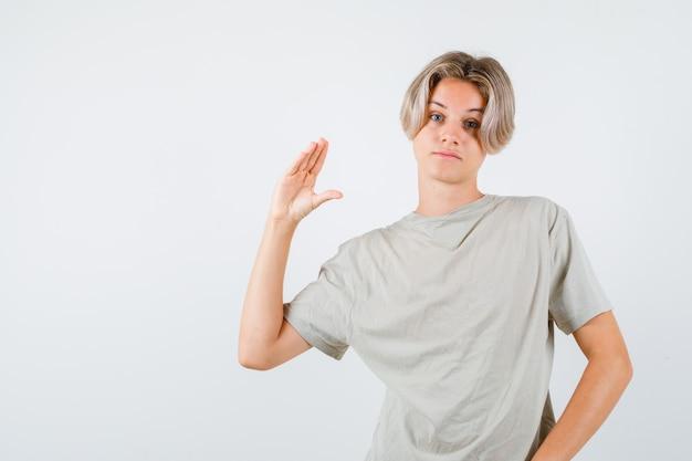 Молодой мальчик-подросток показывает жест бла-бла-бла в футболке и выглядит скучающим