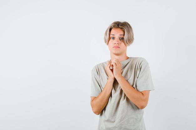 Tシャツで懇願するジェスチャーで握りしめられた手を見せて、がっかりしているように見える若い10代の少年。正面図。