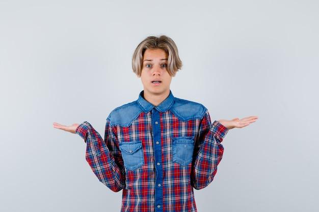 チェックのシャツで無力なジェスチャーを示し、当惑しているように見える若い十代の少年。正面図。