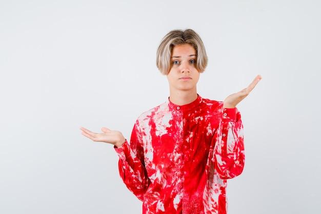 Молодой мальчик-подросток показывает беспомощный жест в рубашке и выглядит смущенным, вид спереди.