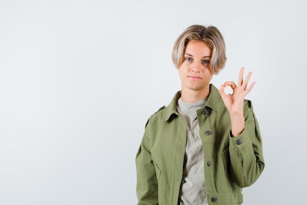 Giovane ragazzo adolescente che mostra gesto ok in maglietta