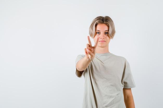 Молодой подросток мальчик показывает жест мира в футболке и выглядит весело. передний план.