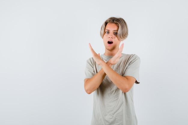Giovane ragazzo adolescente che mostra gesto di rifiuto in maglietta e sembra infastidito. vista frontale.