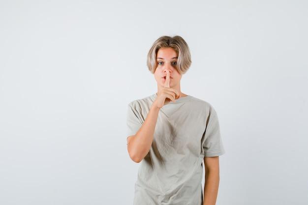 T-셔츠에 침묵 제스처를 보여주고 조심스럽게 찾고 어린 십 대 소년. 전면보기.