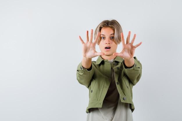 Giovane ragazzo adolescente che mostra il gesto di arresto in maglietta