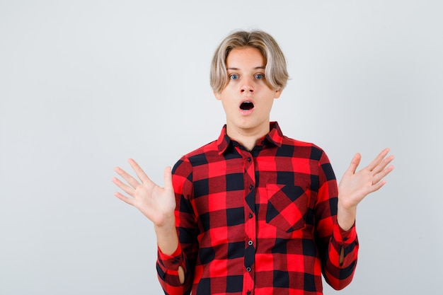チェックのシャツで降伏のジェスチャーを示し、怖がって、正面図を見て若い十代の少年。