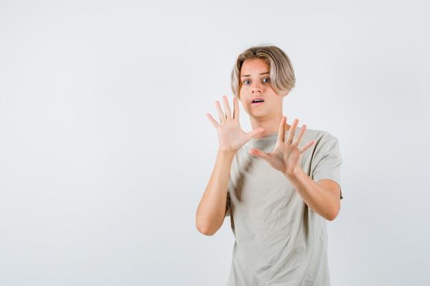 Tシャツで降伏のジェスチャーを示し、おびえた、正面図を見て若い10代の少年。