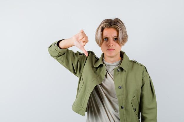Young teen boy showing thumb down in t-shirt