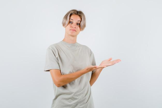 티셔츠에 환영 제스처를 보여주고 부드럽게 보이는 어린 십대 소년. 전면보기.