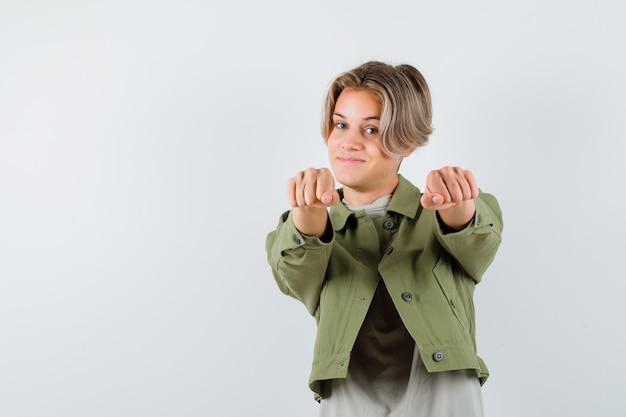Giovane ragazzo adolescente in piedi in posa di lotta in t-shirt