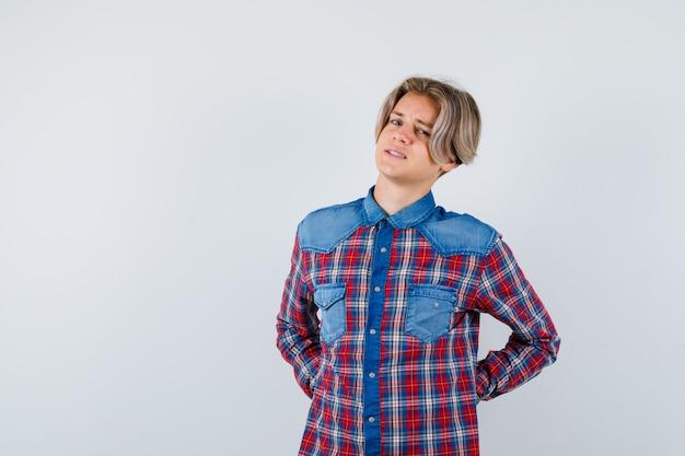 Молодой мальчик-подросток страдает от боли в спине в клетчатой рубашке и выглядит обеспокоенным Premium Фотографии