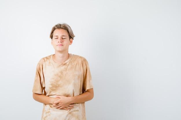 티셔츠를 입은 복통으로 고통받고 몸이 좋지 않은 10대 소년, 앞모습.