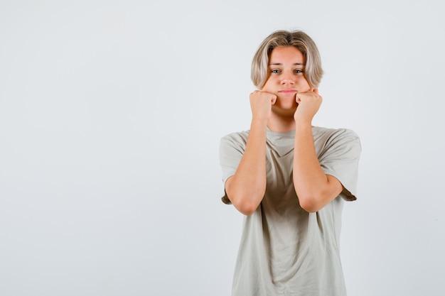 Молодой мальчик-подросток дуется с щеками, опираясь на руки в футболке и выглядит разочарованным
