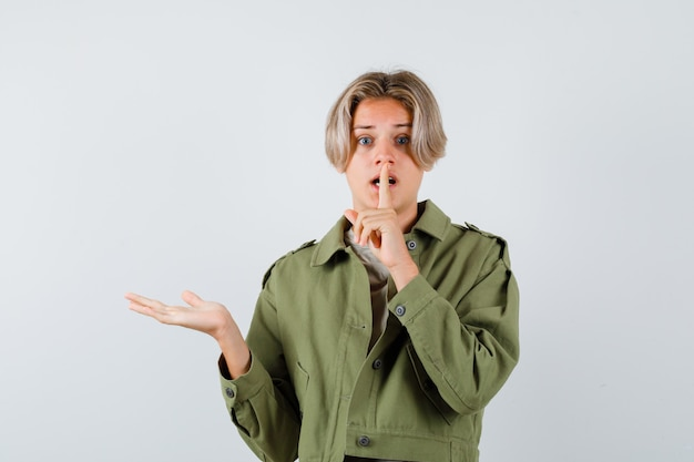 Young teen boy in t-shirt displaying and making silence gesture