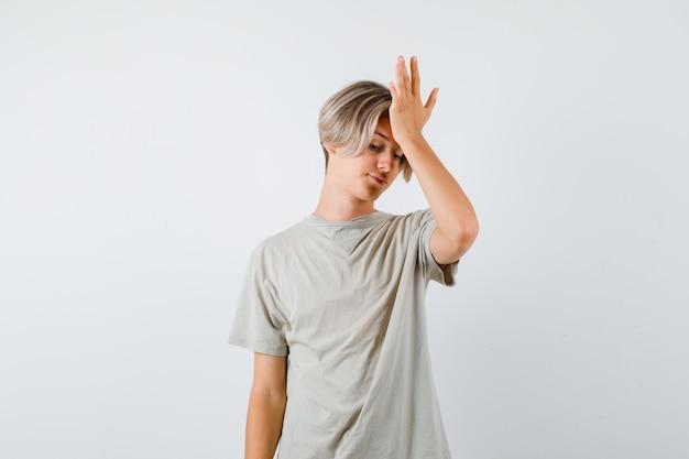 Giovane ragazzo teenager in maglietta che tiene la mano sulla fronte e sembra afflitto, vista frontale.