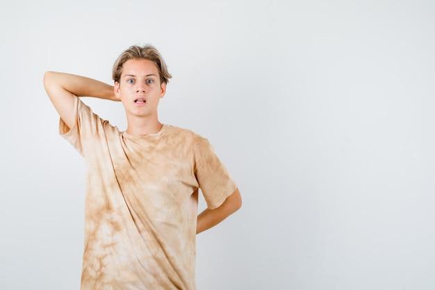 Giovane ragazzo adolescente in maglietta che tiene la mano dietro la testa e la schiena e sembra sconcertato, vista frontale.