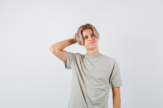 Young teen boy in t-shirt scratching head while looking up and looking pensive , front view.