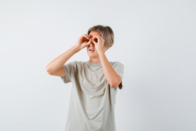 Giovane ragazzo adolescente in maglietta che mostra il gesto degli occhiali mentre distoglie lo sguardo e sembra meravigliato, vista frontale.