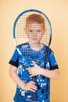 Young teen boy tennis player in motion or movement isolated yellow