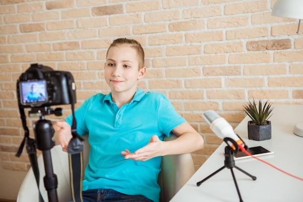 10代の少年のビデオブロガーは、自分のチャンネルのコンテンツを作成しています。幸せな男は、オフィスに座っている間、ユーザーのためにビデオストリーミングを撮影します