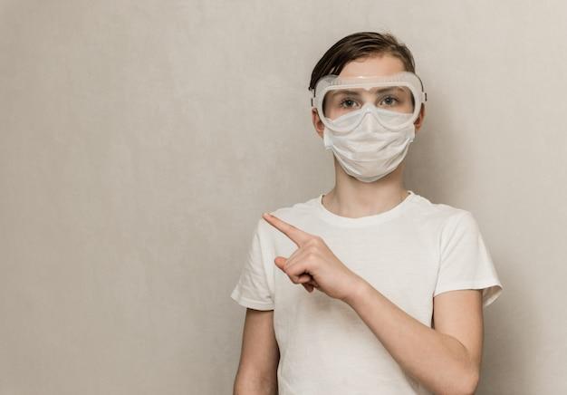 健康マスクを身に着けている若い十代の少年は、灰色の背景に対して人差し指を示しています。コロナウイルスの概念に関する医療情報。新型コロナウイルス