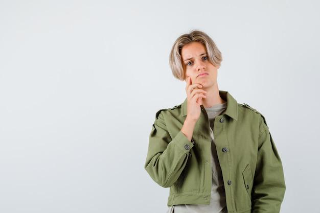 Giovane ragazzo adolescente con il dito sulla guancia in giacca verde e dall'aspetto cupo. vista frontale.