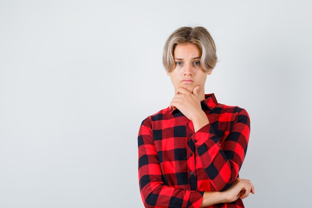 Young teen boy with hand on chin in checked shirt and looking sad , front view.