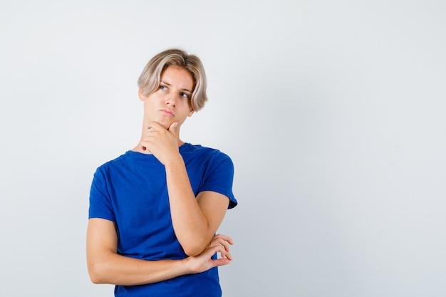 Giovane ragazzo adolescente con la mano sul mento, alzando lo sguardo in maglietta blu e guardando pensieroso. vista frontale.