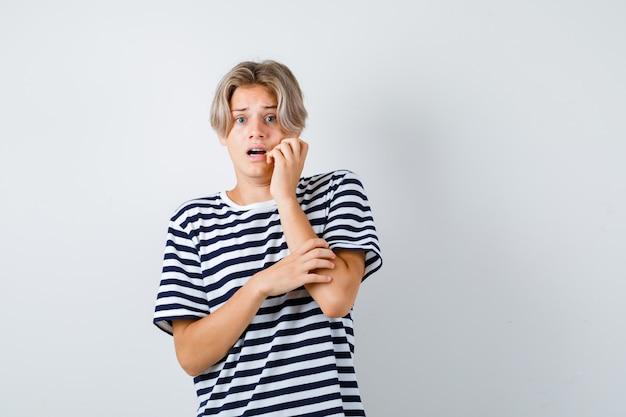 縞模様のtシャツを着て頬に手を持って、おびえているように見える若い10代の少年。正面図。