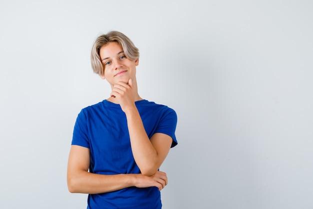 파란색 티셔츠를 입고 턱에 손을 대고 쾌활한 표정을 짓고 있는 어린 10대 소년.