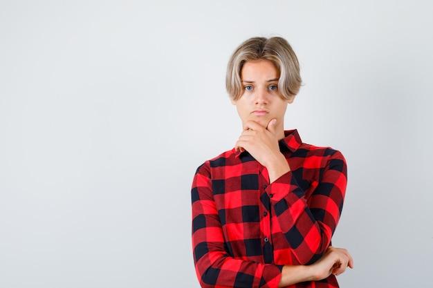 チェックシャツのあごに手を持って、悲しそうに見える、正面図の若い十代の少年。