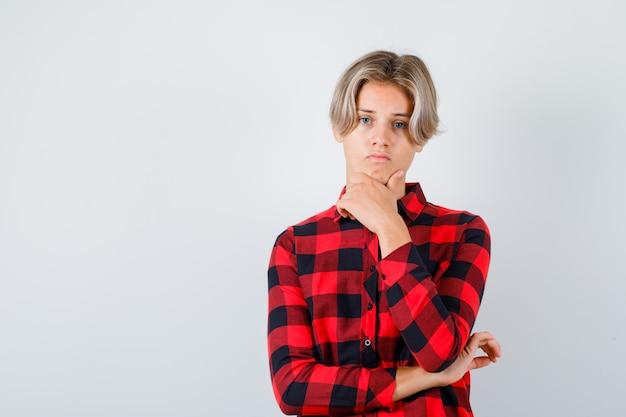 チェックのシャツを着て、あごに手を当てて動揺している若い十代の少年。正面図。
