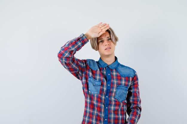 頭に手を持って若い十代の少年