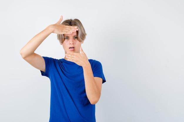 파란색 티셔츠를 입고 머리 위로 손을 얹고 혼란스러워 보이는 어린 10대 소년.