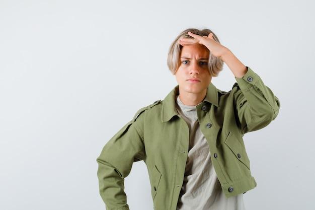 Молодой мальчик-подросток с рукой над головой в зеленой куртке и выглядит смущенным