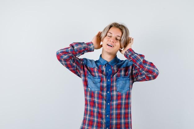 Молодой мальчик-подросток с руками за ушами