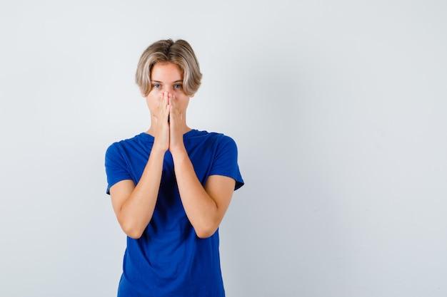 파란색 티셔츠를 입고 기도하는 손에 손을 얹고 희망적으로 보이는 어린 10대 소년. 전면보기.