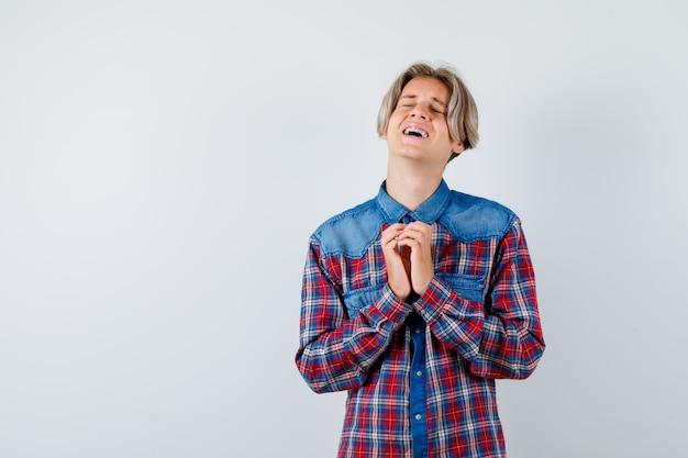 チェックのシャツでジェスチャーを祈り、無力に見える手で若い十代の少年
