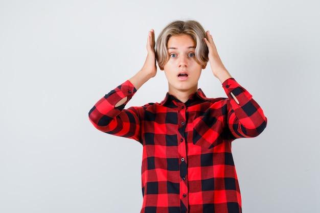 チェックのシャツを着て頭の近くに手があり、怖い、正面図を探している若い十代の少年。