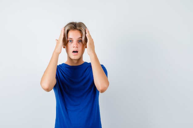 青いtシャツを着て頭に手を当てて、興奮して見える、正面図の若い10代の少年。