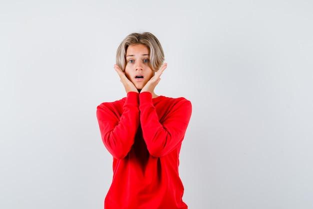 Молодой мальчик-подросток с руками под подбородком в красном свитере и тревожным видом. передний план.