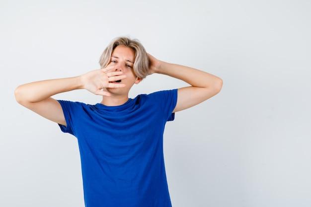 어린 10대 소년이 하품을 하고 파란색 티셔츠를 입고 스트레칭을 하고 졸려 보입니다. 전면보기.