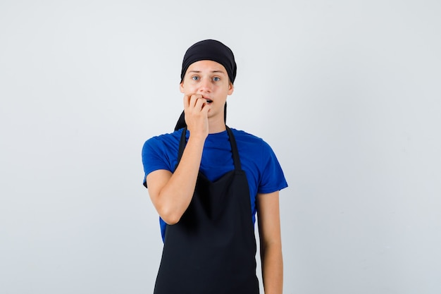 Молодой подросток готовит в футболке, в фартуке эмоционально кусает ногти и выглядит обеспокоенным, вид спереди.