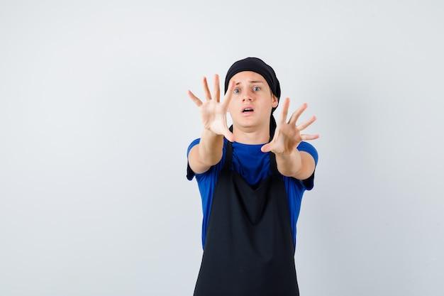Молодой подросток повар в футболке, фартук показывает жест остановки и выглядит испуганным, вид спереди.