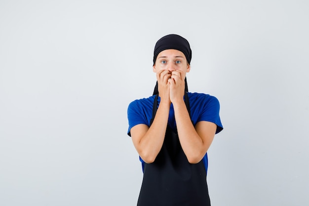 Молодой подросток повар в футболке, фартук с руками во рту и испуганный вид, вид спереди.