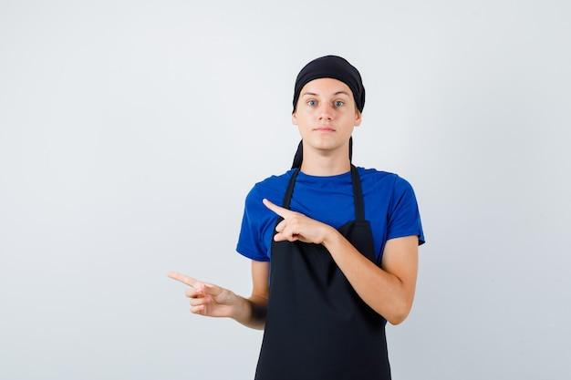 Молодой повар-подросток показывает налево в футболке, фартуке и выглядит умным, вид спереди.