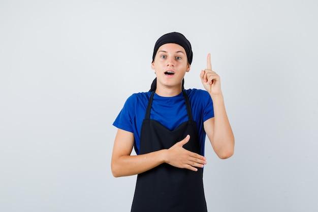 Молодой подросток повар показывает жест эврики, указывая вверх в футболке, фартуке и выглядит умным. передний план.