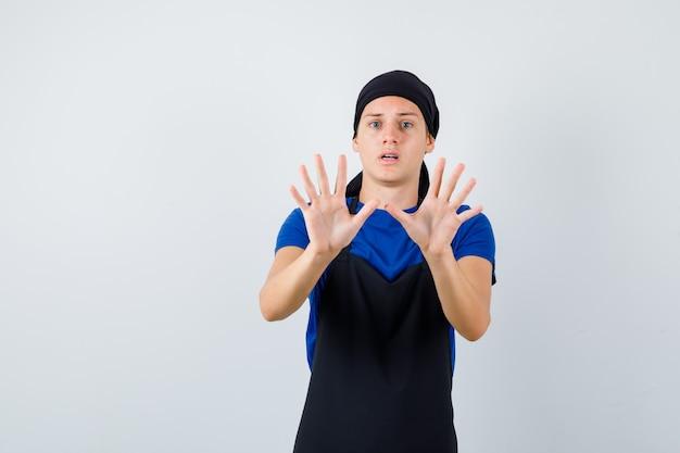Молодой подросток повар показывает жест капитуляции в футболке, фартуке и выглядит испуганным, вид спереди.
